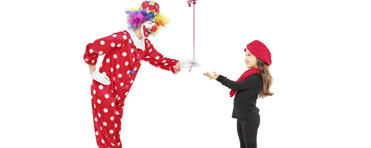 Male clown giving a red balloon to a little girl